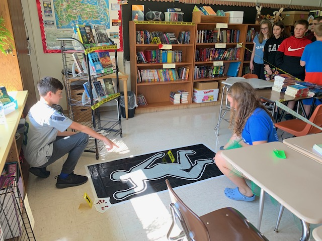 students kneel next to a mock crime scene in a middle school classroom