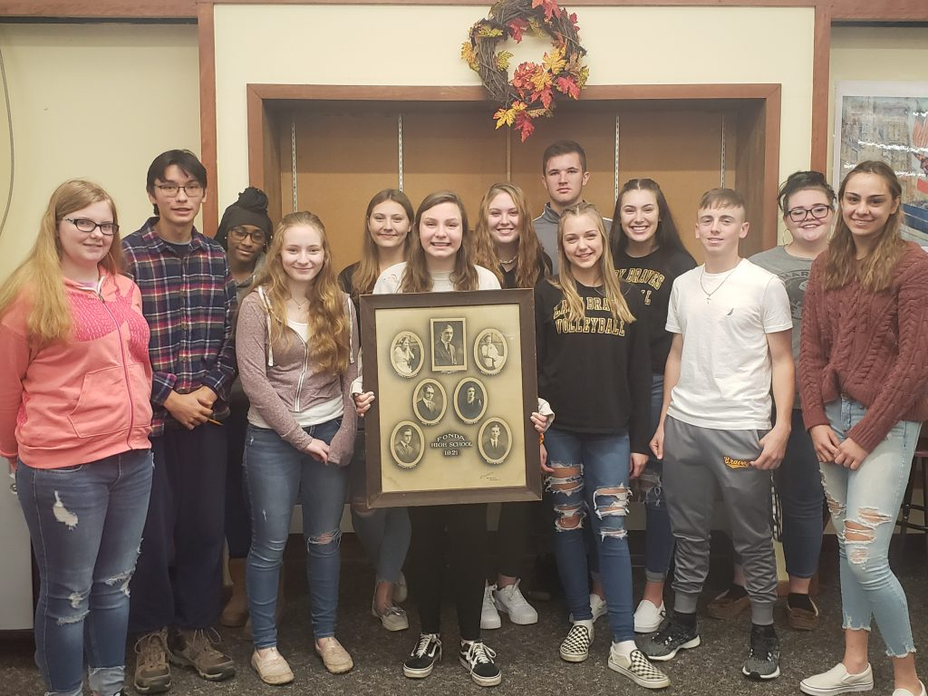 group of high school students pose in a library while holding a picture of the class of 1921