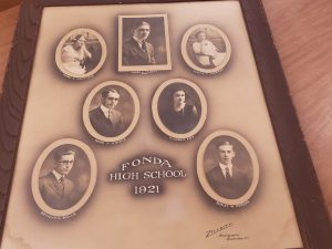 A framed compilation of seven photographs showing the Fonda High School Class of 1921