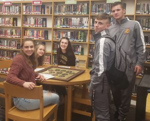 a group of five high school students observe historic photographs at a table in a school library