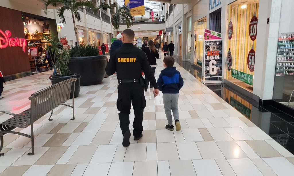 back view of a sheriff's deputy walking through a mall with a third grader