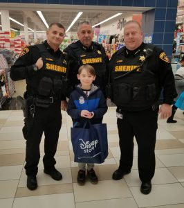 three sheriff's deputies and a third grade pose in a mall