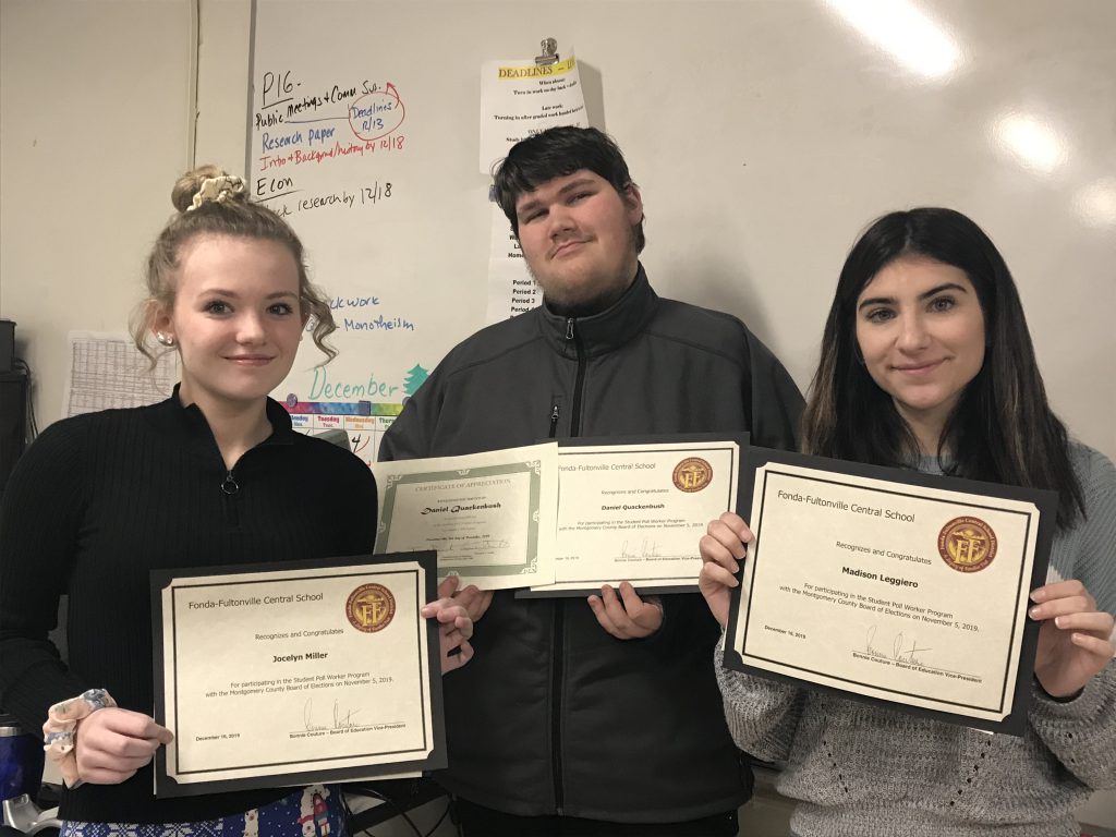 three high school students hold certificates in front of a classroom white board