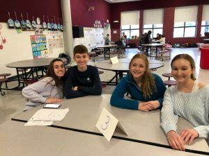 four high school students seated at a table in a school cafeteria