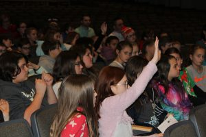 middle school student raises their hand from the audience in a school auditorium