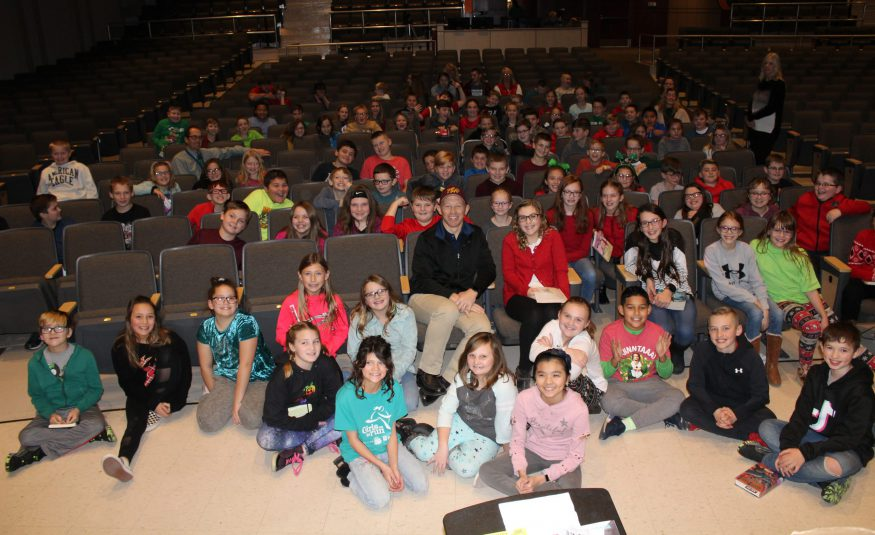 the fifth grade class seated in the audience of a school auditorium with a children's author in the front row