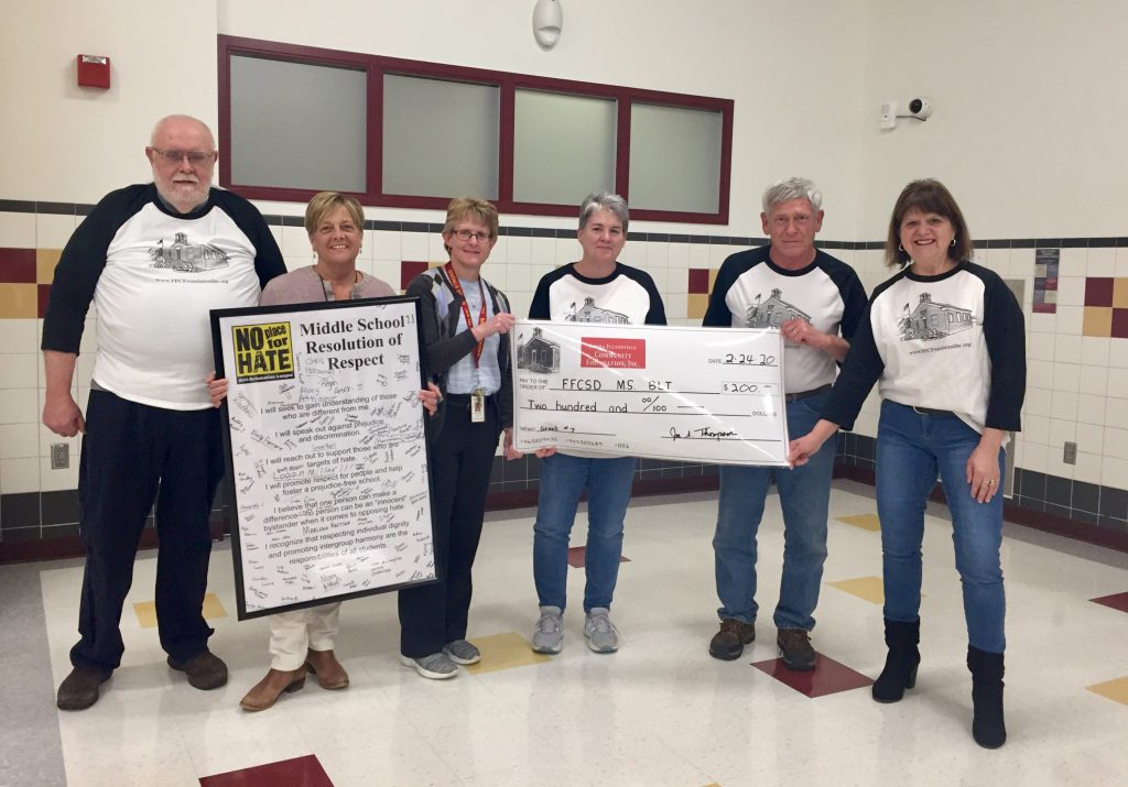 a teacher with members of the community foundation holding a large check display in a school cafeteria