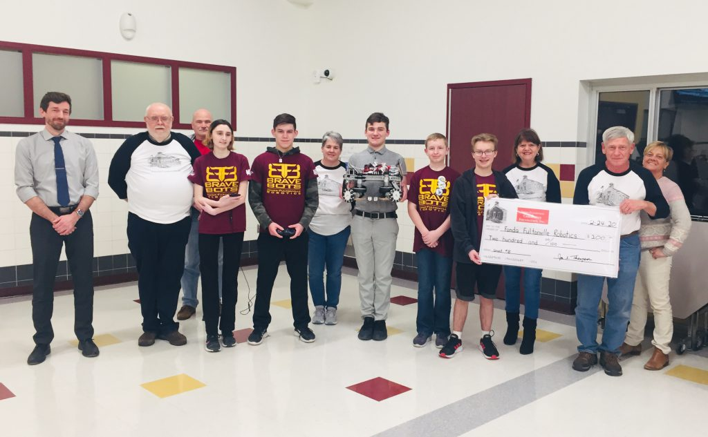 members of a school robotics team with members of the community foundation holding a large check display in a school cafeteria