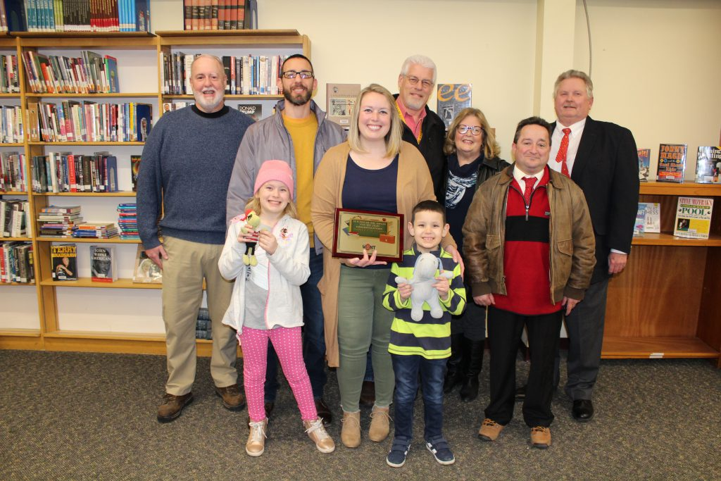 a teacher holds a plaque while flanked by family members and radio station employees in a school library