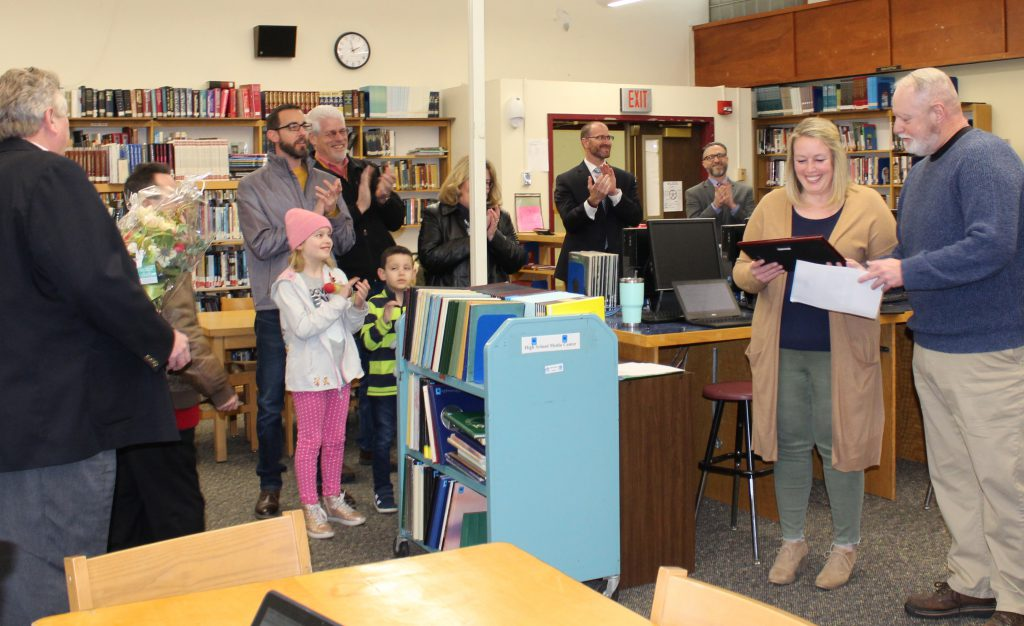 teacher is presented with a plaque from a radio dj in a school library while surrounded by school staff and family members