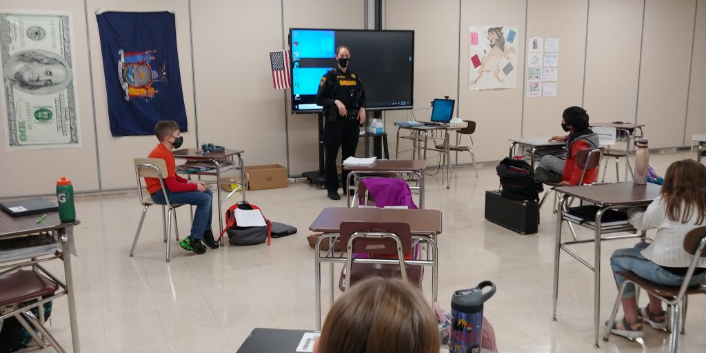 adult in a police uniform stands at the front of a middle school classroom as students are seated in desks