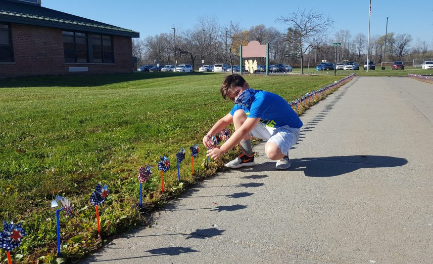 student kneels on a sidewalk outside of a school while placing a pinwheel into the ground