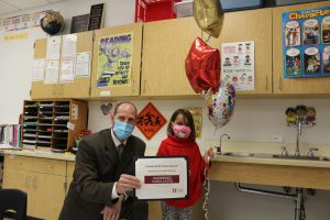 school superintendent and elementary student hold up a certificate and balloons