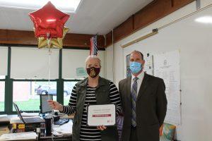 high school math teacher and school superintendent hold up a certificate and balloons