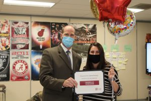 school superintendent and teacher hold up a certificate and balloons