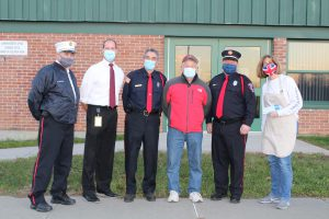 three firefighters, a school superintendent, a community volunteer and a teacher all wearing face masks posing for a photo outside of a school building.