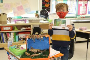 student wearing a mask holds up a paper while standing next to a diorama of a snake habitat