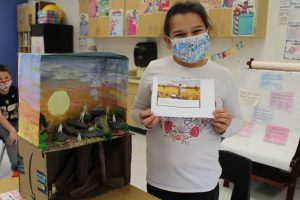 student holds up a paper while standing next to a diorama in a classroom