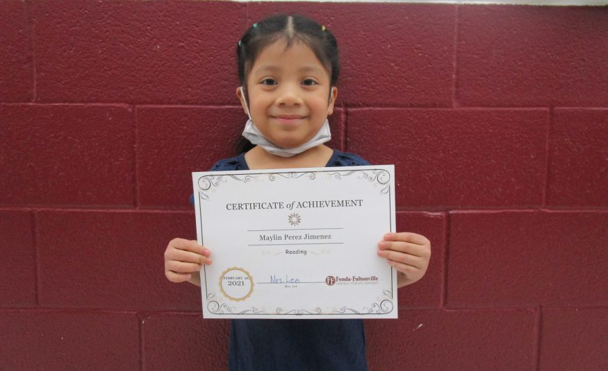 a student with dark hair in pigtails holds an award certificate in a school hallway