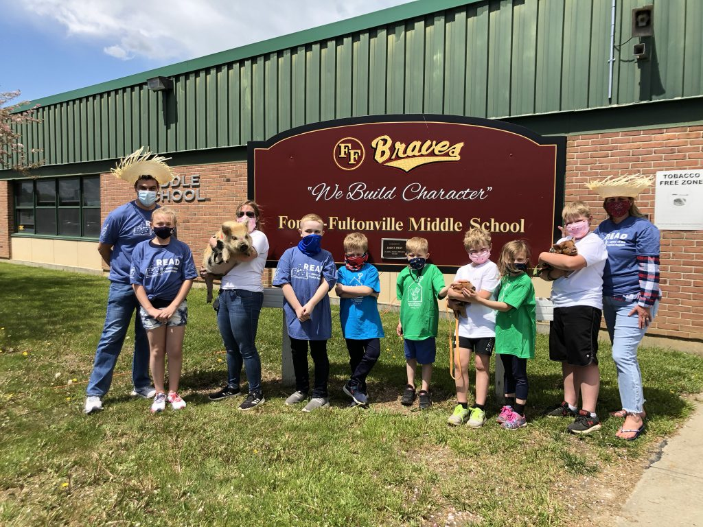 a group of elementary and middle school students stand with their principals outside of the school while holding baby pigs