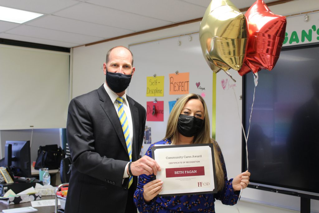 school superintendent stands with a high school teacher holding a certificate and balloons