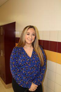 portrait of a high school teacher standing in a school hallway