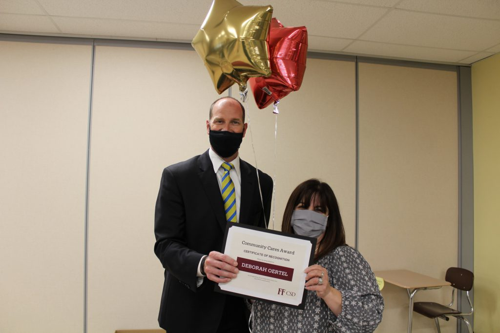 school superintendent stands with a middle school teacher holding a certificate and balloons