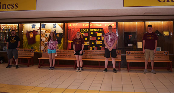 Students stand in front of benches